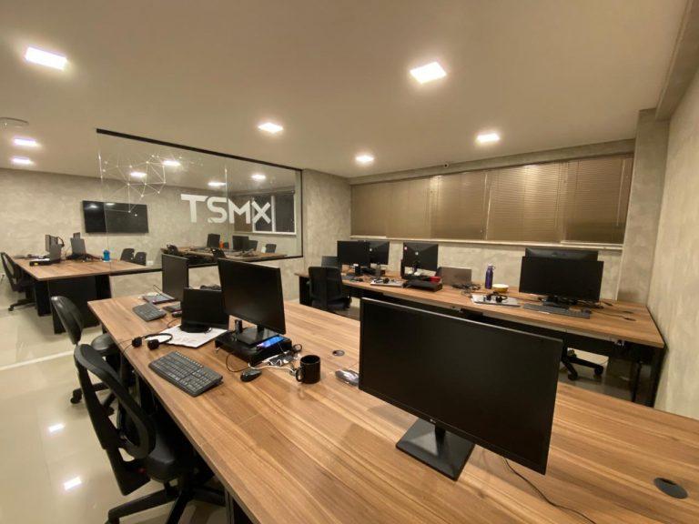 Escritório da empresa TSXM com grandes mesas e grandes computadores